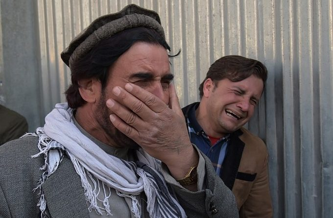 Two Afghan men weep for their relatives in front of the main gate of a military hospital in Kabul on March 8, 2017, after a deadly six-hour attack claimed by the Islamic State group. More than 30 people were killed and around 50 wounded in an insurgent attack on Afghanistan's largest military hospital in Kabul on March 8, the defence ministry said. / AFP PHOTO / SHAH MARAI
