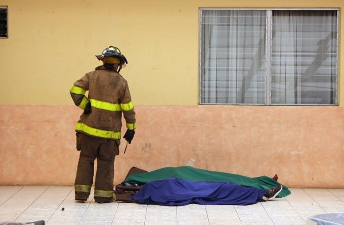 "Handout picture released by Guatemalan Volunteer Firefighters showing a firefighter looking to the corpses of two of the 20 victims of a fire at children's shelter Virgen de la Asuncion facility, in San Jose Pinula, about 10 kilometres east of Guatemala City, on March 8, 2017.  At least 20 teenage girls died in a fire at a children's shelter in Guatemala, a spokesman for the local fire service said. It was not immediately known how many of the bodies were those of children. The center, supervised by state social welfare authorities, hosts minors who are victims of family mistreatment. The facility has been the target of multiple complaints alleging abuse, and several children have run away. / AFP PHOTO / Guatemalan Volunteer Firefighters / HO / RESTRICTED TO EDITORIAL USE - MANDATORY CREDIT ""AFP PHOTO /Guatemalan Volunteer Firefighters /HO "" - NO MARKETING - NO ADVERTISING CAMPAIGNS - DISTRIBUTED AS A SERVICE TO CLIENTS"