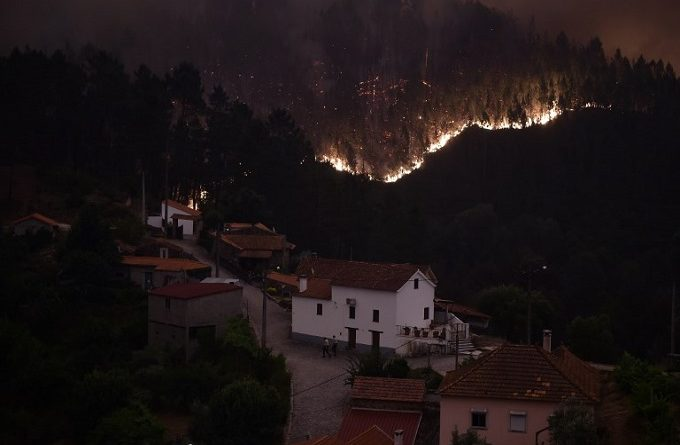 A picture taken on June 18, 2017 shows flames and smoke during a wildfire near the village of Mega Fundeira.  Portugal declared three days of national mourning from June 18, 2017 after the most deadly forest fire in its recent history, raging through the centre of the country. The fire, which broke out June 17, 2017 in the Pedrogao Grande district, had killed at least 62 people and injured more than 50, according to the latest official update by Sunday afternoon.   / AFP PHOTO / MIGUEL RIOPA